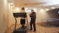 Senior woman running on treadmill on toes in big light room at home. Mature bearded man standing 48030422