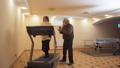 Elderly woman try to run on treadmill and her gray haired husband standing near looks on her with 48030424