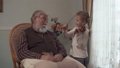 Grandfather sitting with plaid on the rocking chair whil his funny granddaughter dabbling and plays 48031082
