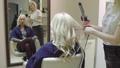 Hairstylist curling woman's hair using hair iron 48038489