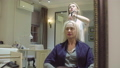 Hairstylist curling woman's hair using hair iron 48038490