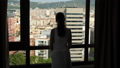 Woman looking on aerial Barcelona cityscape out of window 48060985