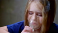 Close up. Portrait of a baby girl with blonde bronchial asthma. Inhalation of medication through a 48090048