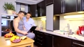 Young cute family having Breakfast at home in the kitchen and watching the news on the laptop 48090057