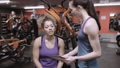 Woman discussing workout progress with instructor 48160819