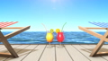 Two tropical drinks and two deckchairs at a seaside 48314843