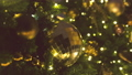 Christmas balls of gold color and garlands with bulbs on the branches of christmas tree, close-up 48436121