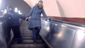 Mom and son in winter clothes are moving down the escalator in the subway tunnel. 48436147