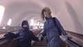 Mom and son in winter clothes are moving up the escalator in the subway tunnel. 48436152