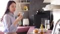 ผู้หญิงกำลังกินอยู่ในขณะที่ดูสมาร์ทโฟน 48470671