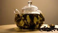 Spinning glass teapot with green tea 48474226