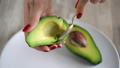 Woman takes out the pulp of the avocado from the peel with a spoon 48487234