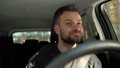 Satisfied bearded man driving a car down the street in sunny weather 48487260