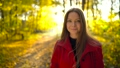 Portrait of a beautiful pensive girl in a red coat with a yellow maple leaf in the background in the 48487504