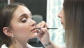 Gorgeous woman is sitting at cosmetic studio with elegance makeup. 48488381