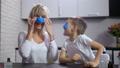 Joyful mom and son sticking handmade slime on face 48524566