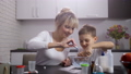 Happy mom with son making slime in home kitchen 48524572