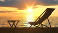 Deck chair and table with glass of wine at seacost against orange sunset 48529684