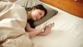 觀看在睡覺蒲團的婦女一個智能手機 48638843
