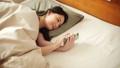 观看在睡觉蒲团的妇女一个智能手机 48642241