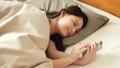 ผู้หญิงกำลังดูสมาร์ทโฟนในฟูกนอน 48677722