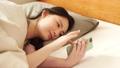 ผู้หญิงกำลังดูสมาร์ทโฟนในฟูกนอน 48677723