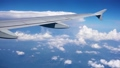 POV view from plane window of blue sky with white clouds from seat near aircraft wing in slow motion 48688612