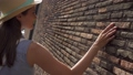 Woman slide hand against old red brick wall in slow motion. Female hand touch rough surface of stone 48688616