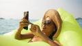 Attractive Young Happy Woman Using Smartphone on Floating Inflatable Mattress at Tropical Beach 48776645