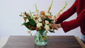 Female florist puts flowers in a glass vase and making a new floral arrangements. Woman picking 48800542