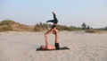 Fit sporty couple practicing acro yoga with partner together on the sandy beach. 48804911