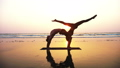 Fit sporty couple practicing acro yoga with partner together on the sandy beach. 48805566