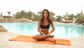 Beautiful positive woman sit at the swimming pool on the orange towel and meditating in yoga pose 48868190