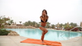 Beautiful positive woman sit at the swimming pool on the orange towel and meditating in yoga pose 48868198