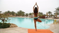 Beautiful positive woman sit at the swimming pool on the orange towel and meditating in yoga pose 48868201