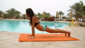 Beautiful positive woman sit at the swimming pool on the orange towel and meditating in yoga pose 48868205