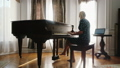 Woman learning to play the piano, looking at laptop screen 48875441