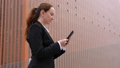 Woman in suit texting in smartphone at city downtown 48877022