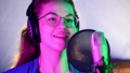 A young smiling woman in headphones singing in the studio. Neon lighting 48895535