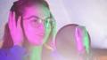 A young woman in headphones singing in the studio. Neon lighting 48895537