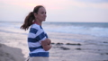 Young woman on sea beach looking at sunset and waves 48899038