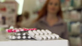 Woman taking blister of pills from the counter at pharmacy, selective focus 48985357