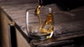 Whiskey pouring in the glass from the bottle. With ice cubes. 49031153