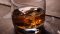 Whiskey rotating in the glass. With ice cubes. 49032523