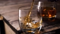 Whiskey pouring in the glass from the bottle. With ice cubes. 49057031