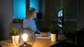 Woman looking attentively at computer at night. Relaxed beautiful blond female in warm home clothing 49064218