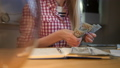 Woman counting cash at working desk. Attractive blond female in checkered shirt sitting at night in 49064221