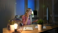 Shocked female at computer talking on smartphone. Sitting in dark room at wooden desk with notebook 49064228