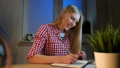 Cheerful female writing in daily planner. Lively young blond woman in casual checkered shirt sitting 49064230