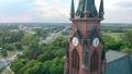 Church in small city among pastures. Drone footage. Red Church is Roman Catholic church. 49064232